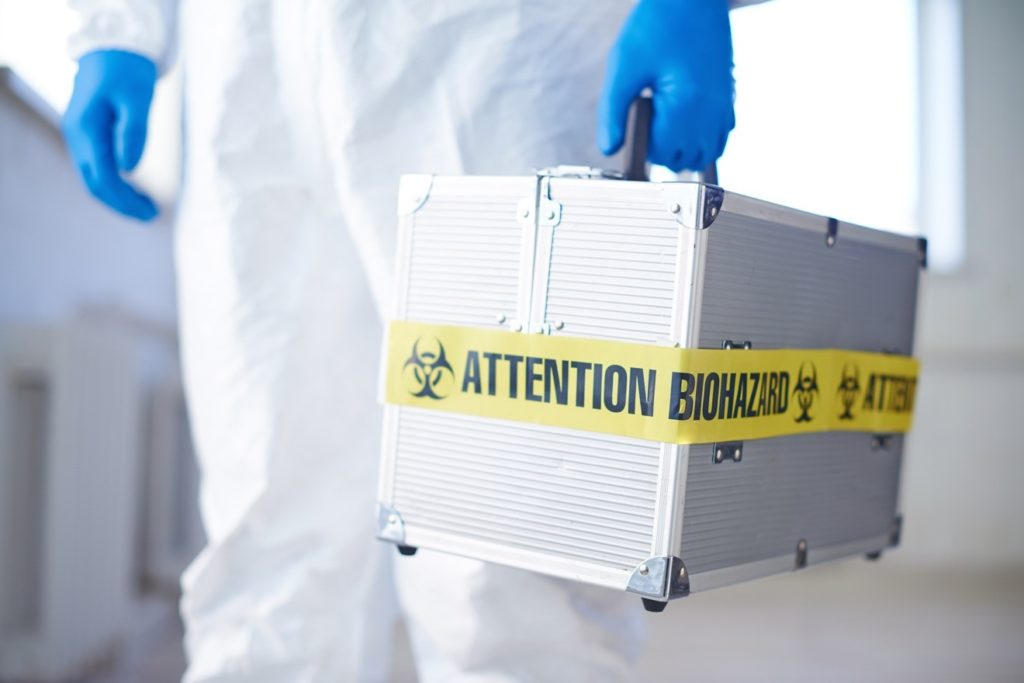 technician with biohazard bag
