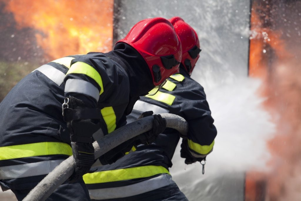 firefighters using a hose to put out a fire
